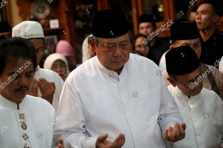 Stock Picture of Former Indonesian President Susilo Bambang Yudhoyono (C) prays in front of his wife. Kristiani Yudhoyono's coffin accompanied by  Former Indonesian President, BJ Habibie (R) at Susilo Bambang Yudhoyono's resident in Cikeas, West Java, Indonesia, 01 June 2019. The wife of former Indonesian President Susilo Bambang Yudhoyono passed away on 01 June 2019 aged 66 at the National University Hospital after losing her battle with blood cancer.