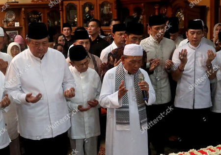 Stock Image of Former Indonesian President Susilo Bambang Yudhoyono (L) prays in front of his wife. Kristiani Yudhoyono's coffin accompanied by Indonesian President, Joko Widodo (3-R), Former Indonesian President, BJ Habibie (2-L) at Susilo Bambang Yudhoyono's resident in Cikeas, West Java, Indonesia, 01 June 2019. The wife of former Indonesian President Susilo Bambang Yudhoyono passed away on 01 June 2019 aged 66 at the National University Hospital after losing her battle with blood cancer.