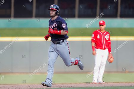 Washington Nationals' Brian Dozier, left, runs the bases after hitting a solo home run off Cincinnati Reds relief pitcher Matt Bowman in the ninth inning of a baseball game, in Cincinnati