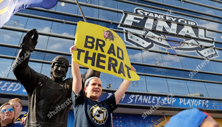 Stock Photo of St. Louis Blues fan Ella Reilly holds a sign featuring a drawing of Boston Bruins left wing Brad Marchand as she stands by a statue of former Blues player Brett Hull before the start of Game 3 of the NHL hockey Stanley Cup Final between the Blues and the Bruins, in St. Louis
