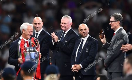 Ian Rush walks with the trophy past FA Chairman Greg Clarke, Tottenham Chairman Daniel Levy and Liverpool owner John W. Henry, who appears to be face-timing one of his daughters