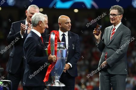Liverpool owner John W Henry facetimes a family member as Ian Rush delivers the Champions League trophy