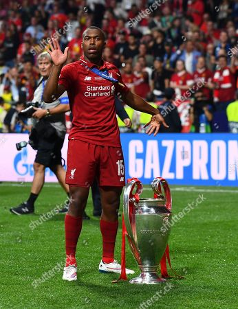 Daniel Sturridge of Liverpool dances with the trophy at his feet