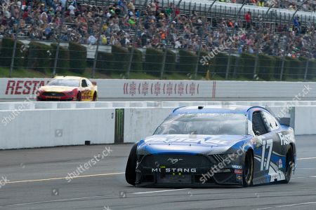 Ricky Stenhouse Jr. drives down pit road after wrecking during a NASCAR Cup Series auto race at Pocono Raceway, in Long Pond, Pa