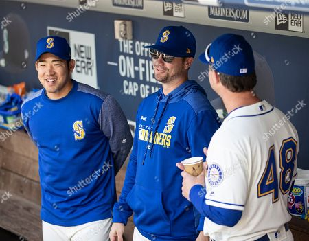Seattle Mariners' Yusei Kikuchi, left, and Wade LeBlanc, center, talk with pitching coach Paul Davis before a baseball game against the Los Angeles Angels, in Seattle