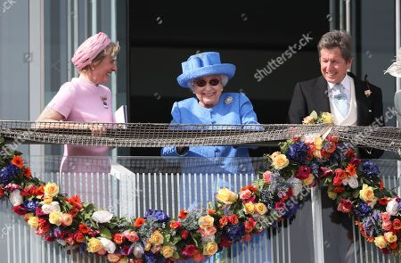 Queen Elizabeth II is all smiles as she watches the Investec Epsom Derby horse racing alongside her horse racing manager John Warren and Julia Budd