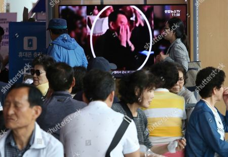People watch a TV screen showing an image of senior North Korean official Kim Yong Chol in a musical performance by the wives of Korean People's Army officers in North Korea during a news program at the Seoul Railway Station in Seoul, South Korea, . A senior North Korean official who had been reported as purged over the failed nuclear summit with Washington was shown in state media on Monday enjoying a concert alongside leader Kim Jong Un