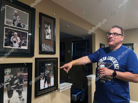 Rob Ferrara points toward photos of his nephew, Patrick Maroon, in his home in St. Louis, Mo., . Patrick Maroon had other offers for more money and more years but chose to sign with his hometown St. Louis Blues. He did it for family: for his young son Anthony, his parents and his grandfather, who then died the day before the team left for the playoffs. That day, Maroon said he'd win the Stanley Cup for his late grandfather Ernie and he and the Blues are two wins away from making a lifelong dream come true