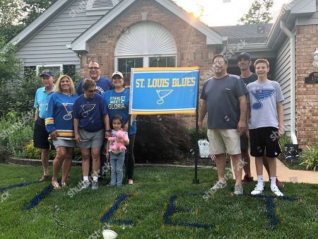Patrick Maroon's family poses for a photo on the lawn of his uncle Rob Ferrara's house, in St. Louis, Mo., . Maroon's mother Patty, is at front left in a Blues jersey. His father is third from right on the other side of the sign. Patrick Maroon had other offers for more money and more years but chose to sign with his hometown St. Louis Blues. He did it for family: for his young son Anthony, his parents and his grandfather, who then died the day before the team left for the playoffs. That day, Maroon said he'd win the Stanley Cup for his late grandfather Ernie and he and the Blues are two wins away from making a lifelong dream come true