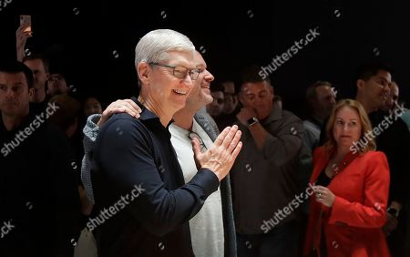 Apple CEO Tim Cook, left, smiles next to chief design officer Jonathan Ive in the display room at the Apple Worldwide Developers Conference in San Jose, Calif