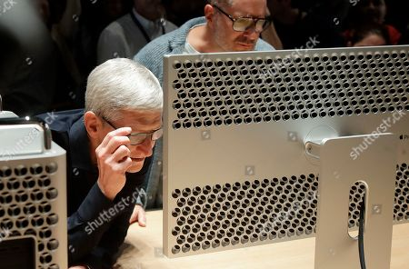 Apple CEO Tim Cook, left, and chief design officer Jonathan Ive look at a Mac Pro in the display room at the Apple Worldwide Developers Conference in San Jose, Calif