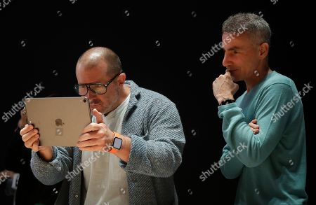 Stock Image of Apple chief design officer Jonathan Ive, left, and senior vice president of hardware engineering Dan Riccio look at the screen of an iPad in the display room at the Apple Worldwide Developers Conference in San Jose, Calif
