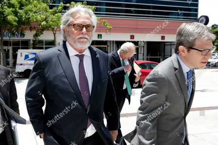 Stock Photo of Carnival Corp. President Micky Arison, left, arrives at federal court, in Miami. Carnival Corp. is in federal court for a hearing on what to do about allegations that it has continued polluting the oceans from some of its cruise ships despite agreeing years ago to stop