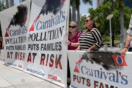 Stock Image of Micky Arison, Arnold Donald. Protestors with Stand.earth hold a banner in opposition to Carnival Corp. outside of federal court, in Miami. Carnival Corp. is in federal court for a hearing on what to do about allegations that it has continued polluting the oceans from some of its cruise ships despite agreeing years ago to stop