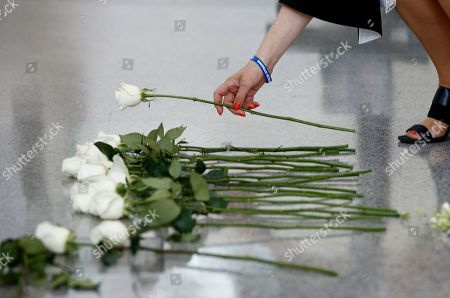 Andrea Chamblee, widow of Capital Gazette journalist John McNamara, places a flower at the foot of the Newseum's Journalists Memorial in Washington, during a rededication ceremony. McNamara, who was killed by a gunman who attacked the paper's newsroom in June 2018, was one of 21 journalists' names added to the memorial to represent all journalists who lost their lives around the world in 2018