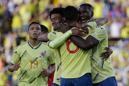 Colombia's William Tesillo, back to camera, is congratulated by teammates Cristian Zapata, right, and Juan Guillermo Cuadrado, left, after scoring a goal during a friendly soccer match against Panama at El Campin stadium in Bogota, Colombia
