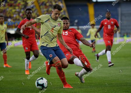 Colombia's Santiago Arias, front, battles for the ball with Panama's Eric Davis during a friendly soccer match at El Campin stadium in Bogota, Colombia