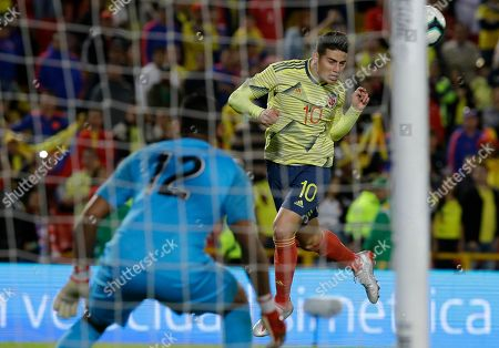 Colombia's James Rodriguez heads the ball as Panama's goalkeeper Jose Calderon stands alert during a friendly soccer match at El Campin stadium in Bogota, Colombia