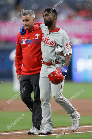 Philadelphia Phillies' Andrew McCutchen, center, is helped by a trainer after being injured trying to get back to first base during the first inning of a baseball game against the San Diego Padres, in San Diego