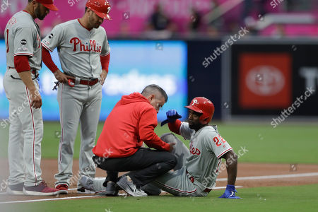 Stock Photo of Philadelphia Phillies' Andrew McCutchen, right, is helped by a trainer after being injured trying to get back to first base during the first inning of a baseball game against the San Diego Padres, in San Diego. Philadelphia Phillies manager Gabe Kapler, left, looks on alongside first base coach Paco Figueroa