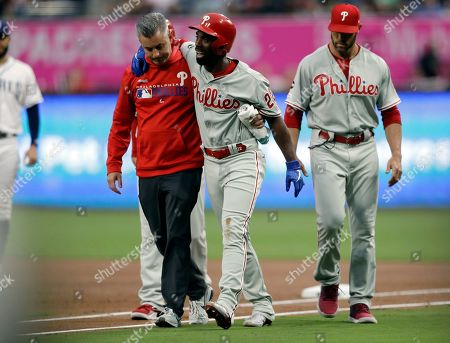 Philadelphia Phillies' Andrew McCutchen, center, is helped by a trainer after being injured while trying to get back to first base during the first inning of a baseball game against the San Diego Padres, in San Diego. Phillies manager Gabe Kapler, right, looks on
