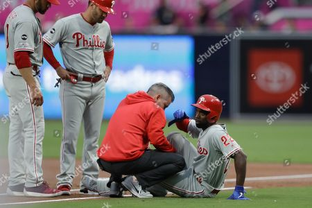 Stock Picture of Philadelphia Phillies' Andrew McCutchen, right, is helped by a trainer after being injured while trying to get back to first base during the first inning of a baseball game against the San Diego Padres, in San Diego. Phillies manager Gabe Kapler, left, watches alongside first base coach Paco Figueroa