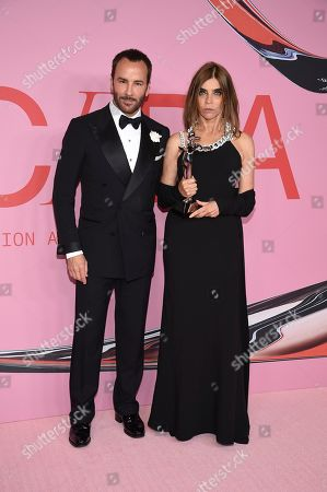 Stock Image of Tom Ford, Carine Roitfeld. Tom Ford, left, and honoree Carine Roitfeld pose in the winner's walk with the Founder's award in honor of Eleanor Lambert at the CFDA Fashion Awards at the Brooklyn Museum, in New York