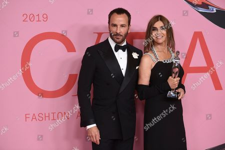 Tom Ford, Carine Roitfeld. Tom Ford, left, and honoree Carine Roitfeld pose in the winner's walk with the Founder's award in honor of Eleanor Lambert at the CFDA Fashion Awards at the Brooklyn Museum, in New York