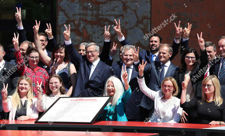 Poland's opposition politicians, including former presidents Bronislaw Komorowski, center, and Aleksander Kwasniewski, center right, along with European Council head Donald Tusk, who was Poland's prime minister, right, flash Victory signs as they celebrate 30 years since parliamentary elections that ousted communists from power, in Gdansk, Poland