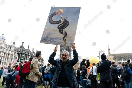 Satirical artist Kaya Mar poses with his recent artwork depicting Donald Trump suppressing press freedom in Parliament Square on the second day of Donald Trump's three-day state visit to the United Kingdom.