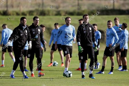 Uruguay's goalkeepers, front from left, Martin Campana, Martin Silva, captain Diego Godin, and goalkeeper Fernando Muslera, walk on the field during a national soccer team training session in the outskirts of Montevideo, Uruguay, . Uruguay will face Panama on a friendly match on June 7