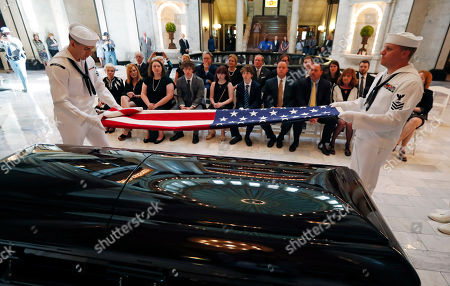 Family members watch as a Navy honor guard from Naval Air Station-Meridian, fold the American flag that was draped on the coffin of the late Republican senator Thad Cochran, prior to presentation to his widow at the Mississippi State Capitol in Jackson, Miss., . Cochran was 81 when he died Thursday in a veterans' nursing home in Oxford, Mississippi. He was the 10th longest serving senator