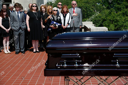Family members watch as the coffin of the late Republican senator Thad Cochran, is taken out of the Capitol in Jackson, Miss., . Cochran was 81 when he died Thursday in a veterans' nursing home in Oxford, Mississippi. He was the 10th longest serving senator