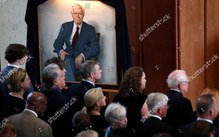 A portrait of the late Republican senator Thad Cochran, looms over family members, during funeral services at Northminster Baptist Church in Jackson, Miss., . Cochran was 81 when he died Thursday in a veterans' nursing home in Oxford, Mississippi. He was the 10th longest serving senator
