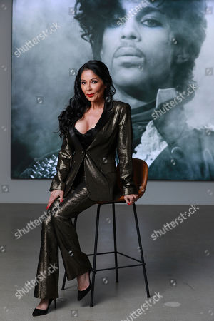 "Apollonia Kotero, a former protege and longtime friend of Prince, poses in front of a portrait of the artist at Warner Music Group in Los Angeles on . Kotero said Prince's untimely death in 2016 sent her into a ""rabbit hole of severe depression"