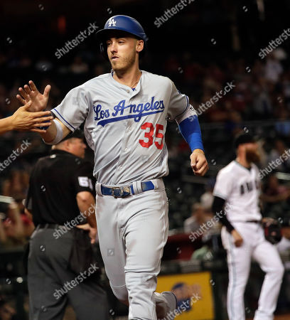 Los Angeles Dodgers' Cody Bellinger is congratulated after scoring on a two-run double by David Freese during the ninth inning of the team's baseball game against the Arizona Diamondbacks, in Phoenix