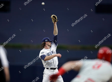 San Diego Padres starting pitcher Chris Paddack can't reach the ball hit by Philadelphia Phillies' Bryce Harper during the first inning of a baseball game, in San Diego. Harper grounded out to shortstop Manny Machado on the play