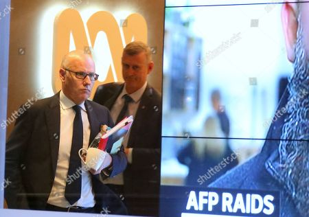 John Lyons (L), Executive Editor of the ABC News, is followed by an Australian Federal Police officer as they walk out the main entrance to the ABC building located at Ultimo in Sydney, New South Wales, Australia, 05 June 2019. Federal police officers have raided ABC's Sydney offices over a series of stories published in 2017, known as 'The Afghan Files', that suggested Australian troops may have committed war crimes.