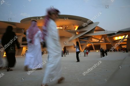 Stock Image of People visit the National Museum of Qatar in Doha, Qatar. Designed by French architect Jean Nouvel, it was inspired by the desert rose crystal and opened on March 28th