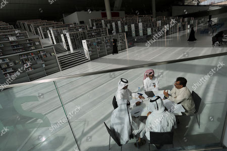 Stock Picture of Students listen to their professor at the Qatar National Library in Doha, Qatar. The 45,000-square-meter building designed by architect Rem Koolhaas has climate-controlled display cases in the Heritage Library