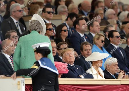 President Donald Trump, center, smiles as British Prime Minister Theresa May after she spoke on stage during an event to mark the 75th anniversary of D-Day in Portsmouth, England . World leaders including U.S. President Donald Trump are gathering Wednesday on the south coast of England to mark the 75th anniversary of the D-Day landings. An image of WWII U.S. President Franklin D. Roosevelt is shown, right