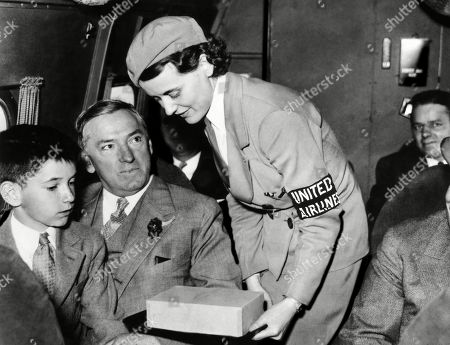 United Airlines stewardess assists Mayor James Curley of Boston. He went on to become the governor of Massachusetts, 1934. Courtesy: CSU Archives/Everett Collection