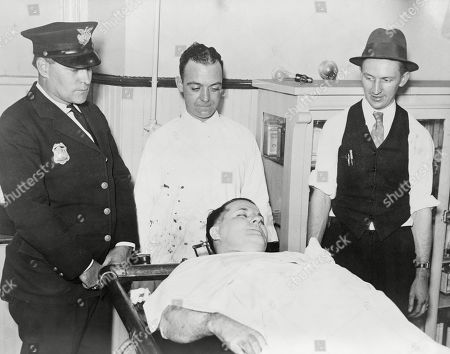 Dead body of Charles Pretty Boy Floyd (1904-1934) on a gurney with police officers Robert Pyle and George Curran, and undertaker Frank Dawson standing nearby. He was shot dead by Melvin Purvis and other FBI agents. Channing Tatum played Pretty Boy Floyd in the 2009 film, PUBLIC ENEMIES.