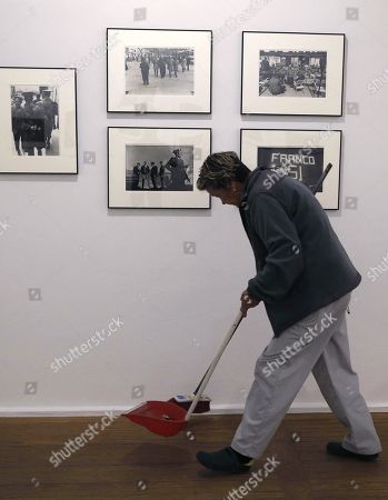 A cleaning worker sweeps in front of photographs by US photographer Joel Meyerowitz on display during the exhibition 'Into the Light', in Madrid, Spain, 06 June 2019. The event features 98 photographs showing the social, cultural and political situation in Spain from 1966 to 1967 will be open to public from 05 June to 31 July 2019.