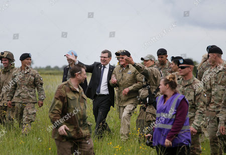 People guide U.S. World War II D-Day veteran Tom Rice, from Coronado, CA, center, after he parachuted in a tandem jump into a field in Carentan, Normandy, France, . Approximately 200 parachutists participated in the jump over Normandy on Wednesday, replicating a jump made by U.S. soldiers on June 6, 1944 as a prelude to the seaborne invasions on D-Day
