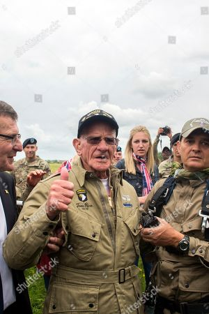 U.S. World War II D-Day veteran Tom Rice, from Coronado, CA, gives the thumbs up after parachuting in a tandem jump into a field in Carentan, Normandy, France, . Approximately 200 parachutists participated in the jump over Normandy on Wednesday, replicating a jump made by U.S. soldiers on June 6, 1944 as a prelude to the seaborne invasions on D-Day
