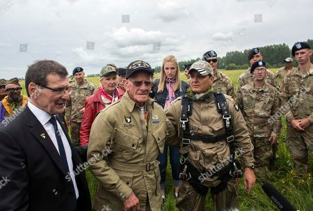 U.S. World War II D-Day veteran Tom Rice, from Coronado, CA, front second left, is guided after parachuting in a tandem jump into a field in Carentan, Normandy, France, . Approximately 200 parachutists participated in the jump over Normandy on Wednesday, replicating a jump made by U.S. soldiers on June 6, 1944 as a prelude to the seaborne invasions on D-Day