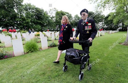 Canadian World War II veteran Bill Anderson walks past headstones at the Beny-sur-Mer Canadian War Cemetery in Reviers, Normandy, France, . A ceremony was held on Wednesday for Canadians who fought and died on the beaches and in the bitter bridgehead battles of Normandy during World War II