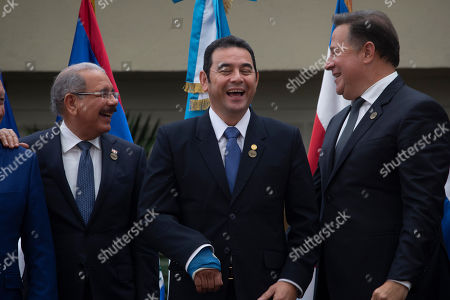 Guatemalan president Jimmy Morales, center, listens to Panama's President Juan Carlos Varela, right, accompanied by Dominican Republic President Danilo Medina during a photo opportunity of the Central America Integration System (SICA) summit in Guatemala City, . Presidents and heads of delegations discuss migration, cooperation and the economy