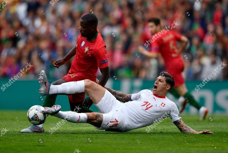 Portugal's William Carvalho, left, and Switzerland's Steven Zuber, right, challenge for the ball during the UEFA Nations League semifinal soccer match between Portugal and Switzerland at the Dragao stadium in Porto, Portugal